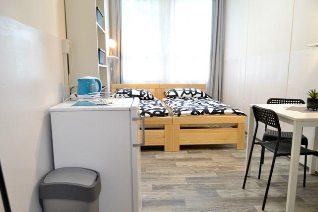 Postel a krásně prosvětlená místnost v brněnské ubytovně